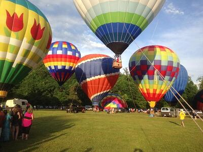 6 hot air ballons on the ground getting ready for take off