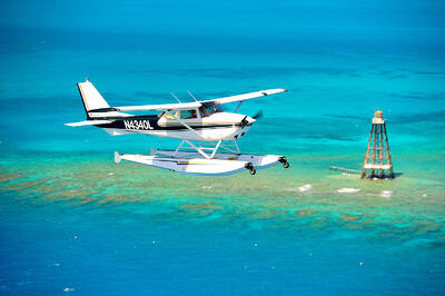 blue and white seaplane flying over the ocean