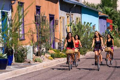 four girls riding bike by colorful houses