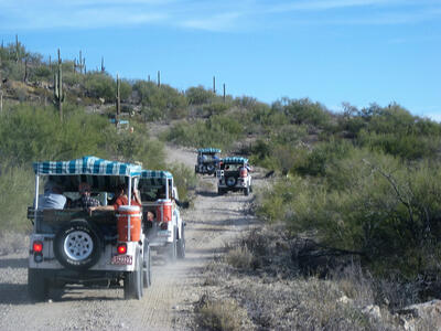 four jeeps driving on a dusty road in tucson