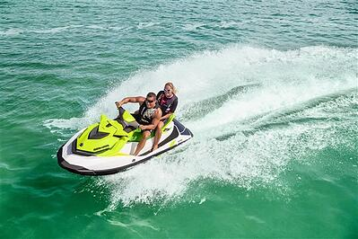 yellow jet ski with 2 people on it